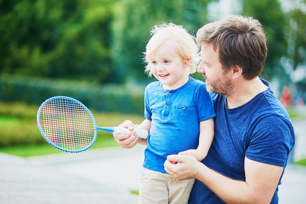 bimbo-e-adulto-con-racchetta-tennis