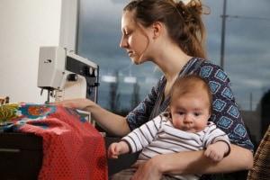 mamma-che-cuce-con-bambino-in-braccio