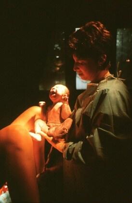 m8100190-natural_childbirth_doctor_holds_newborn_baby_boy
